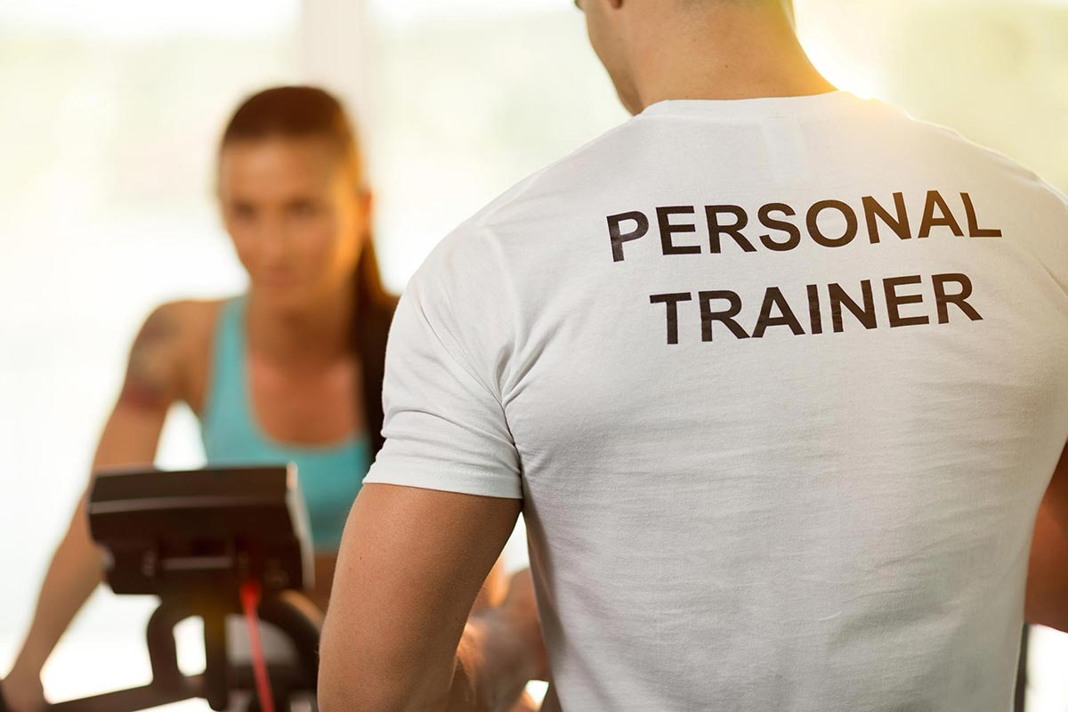 Personal trainer in foregroud with out of focus client on exercise bike
