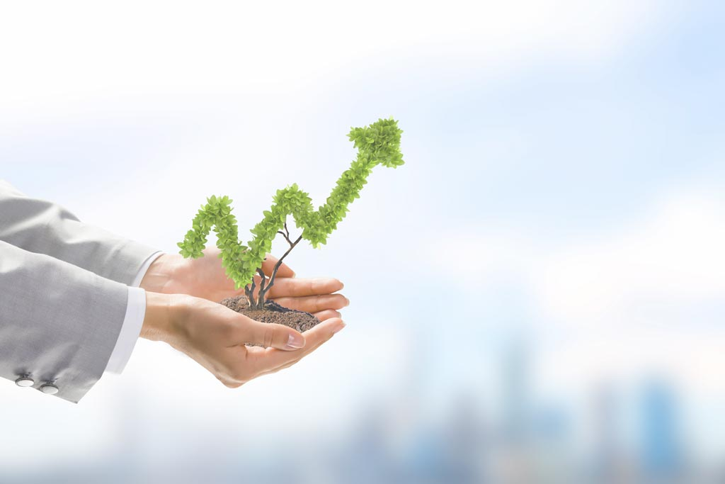 hands of person in suit holding miniature tree in shape of upward trend graph