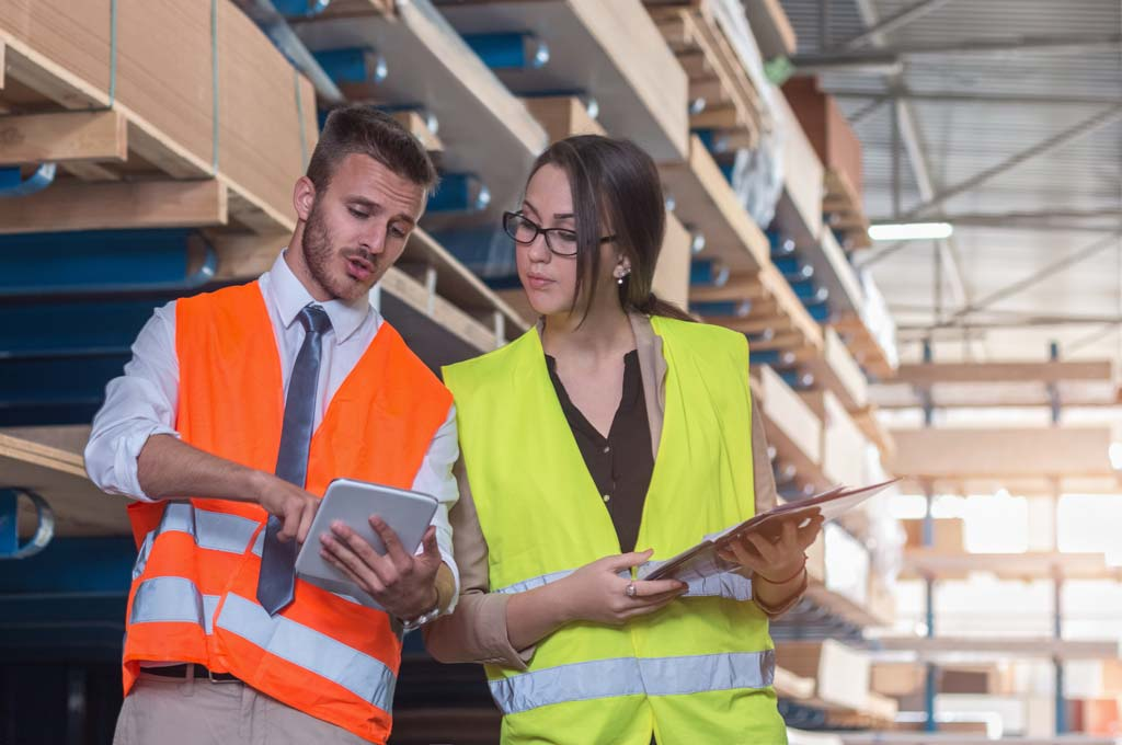 two colleagues wearing high visibility jackets and talking in large warehouse while looking at tablet computer