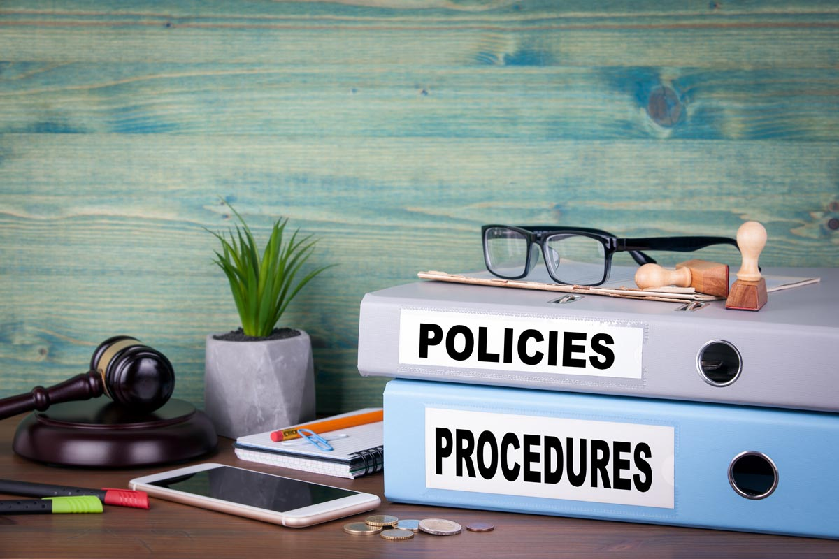 2 ring binders laying on a table with policies and procedures written on the side